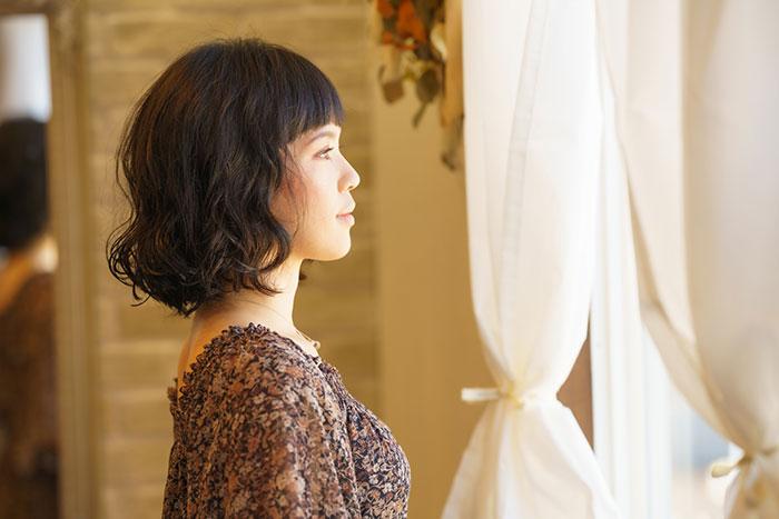 窓外に目を向ける女性の写真