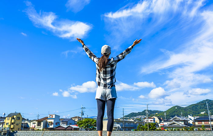 青空に手を広げる女性の写真